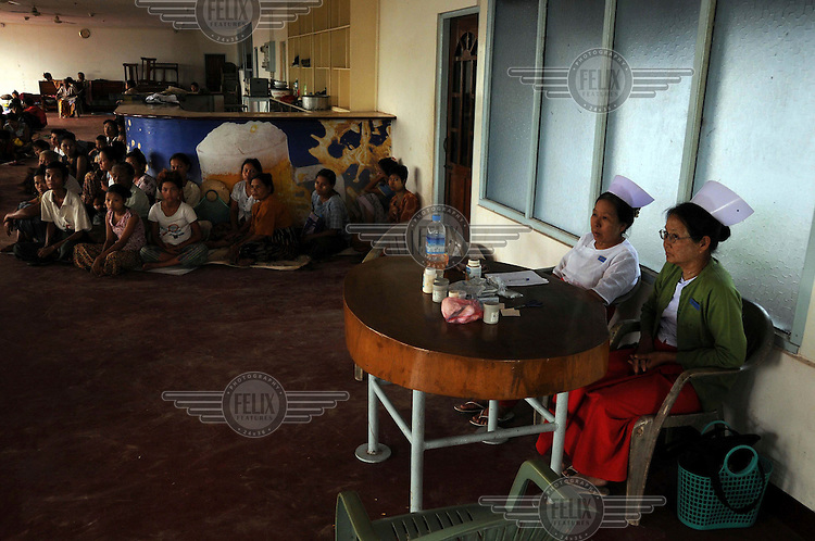 People who lost their homes in the cyclone shelter in a beer station (pub) in Thanlyin. Although the owner has sanctioned this, the authorities have decreed that everyone will have to move out tomorrow, as it reflects poorly on Myanmar's image. Government nurses monitor the 'guests'. Cyclone Nargis struck Burma on 02/05/2008.