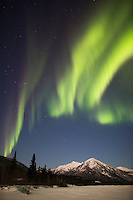 Green curtains of the northern lights over the foothills of the Brooks Range Mountains, Arctic, Alaska.