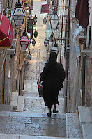 Woman walking down the steps of a steep narrow street strewn with lamps in the Old Town of Dubrovnik, Croatia. The city developed as an important port in the 15th and 16th centuries and has had a multicultural history, allied to the Romans, Ostrogoths, Byzantines, Ancona, Hungary and the Ottomans. In 1979 the city was listed as a UNESCO World Heritage Site. Picture by Manuel Cohen