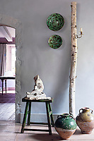 In the cloud-blue entrance hall an unusual light has been created using a candle sconce and a birch tree trunk
