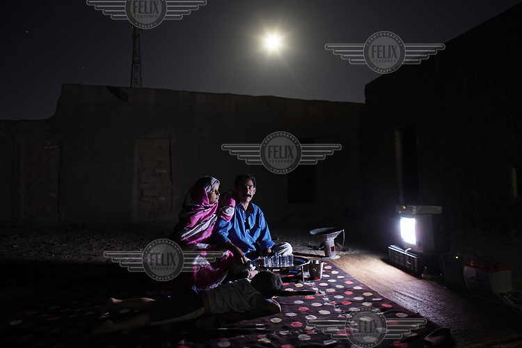 Ali Salem Salma, 41, statistician for the Saharawi government. Pictured watching TV at home with his wife, Nabba, and four year old son, Khadda, in Smara refugee camp, Algeria: 'I was born in El Aaiun in October 1968. In 1975 we built a house in Zemla, a neighbourhood of the city. At the end of '75 Morocco invaded our cities during the Green March and the Moroccan soldiers told us to leave our house. Moroccan civilians moved into all the homes. We spent six months travelling to Algeria to the refugee camps and we are still here. We still have a key to our house we even have papers to prove it belongs to us. I went to Libya in 1976. They were good to us and really helped us with food and clothes and educated us very well. I went to university in Algeria and in 1992, graduated with a degree in statistics and returned to the camps to work for the Saharawi government. Our lives here are simple, we know there are better ways to live but we must be very well organised in order to survive here. Now I send my children to school and maybe they can travel to study at a university but even if they get a degree they will return here and have nothing because there is no possibility of a job.'.
