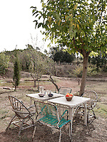 A pair of white wooden tables and four old, wood and metal chairs create an eating area in the garden