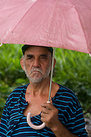 An old man watches football standing under a pink umbrella at Jardim São Marcos favela, Cubatão