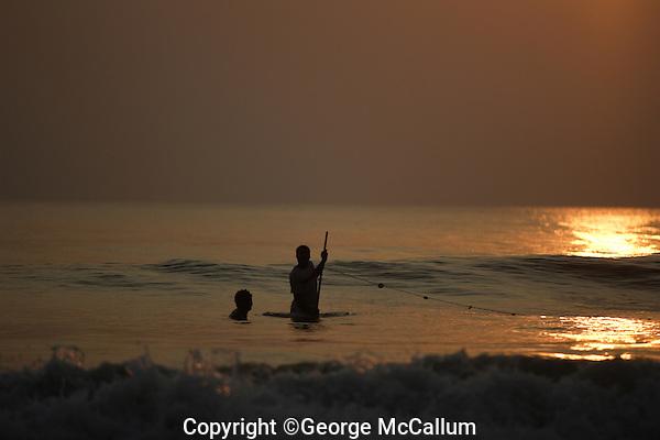 Pair of Beach fishermen pulling one end of Gill net through surf, Goa, Arabian sea, India.