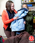 WATERBURY, CT.18 January 2010-011810SV11--From left, Enkelejda Ago, 16, of Waterbury helps Pauleen Lavette pick out a coat at the Waterbury Baptist Ministries in Waterbury. Waterbury students  handed out lunches and winter items to the homeless at Waterbury Baptist Ministries, while providing the homeless a warm place to spend the day Monday.<br /> <br /> Steven Valenti Republican-American