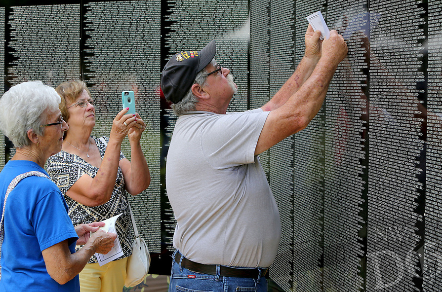 NWA Democrat-Gazette/DAVID GOTTSCHALK  Vel Hornberger (from left) and Linda Evans watch Vietnam War and Marine Corp Veteran David Evans locate the name Thursday, May 18, 2017, of a friend's name on the Vietnam Veterans Memorial The Moving Wall following opening ceremonies on the campus of the Veterans Health Care System of the Ozarks in Fayetteville. The wall has been touring the country for more than 30 years and will on the camus through Monday, May 22. The Moving Wall is a half scale replica of the memorial in Washington D.C..
