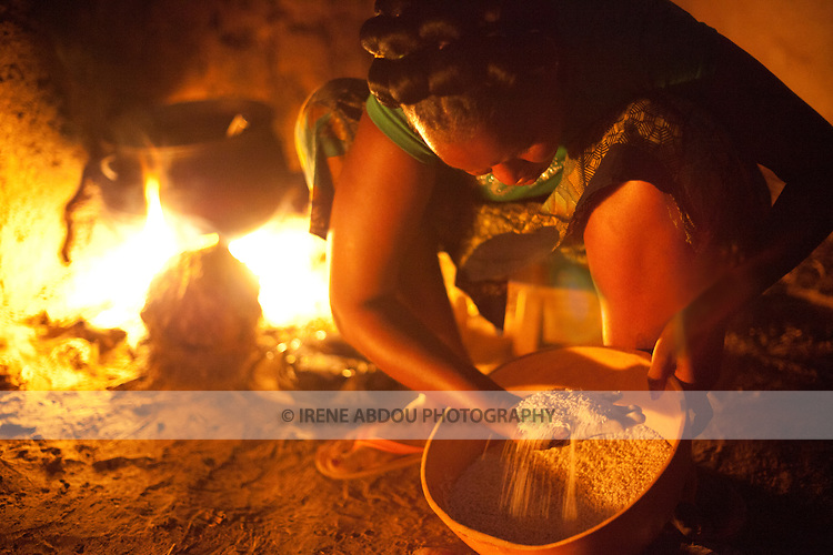 A woman in Djibo in northern Burkina Faso inspects grains of millet that will be cooked for dinner.  Without a stove or electricity, women throughout West Africa cook outside on an open fire.