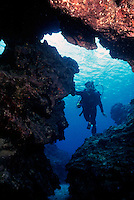 DIVER IN GROTTO<br /> Monitoring Coral Reef<br /> Diver explores reef in search of marine life with underwater photography equipment.