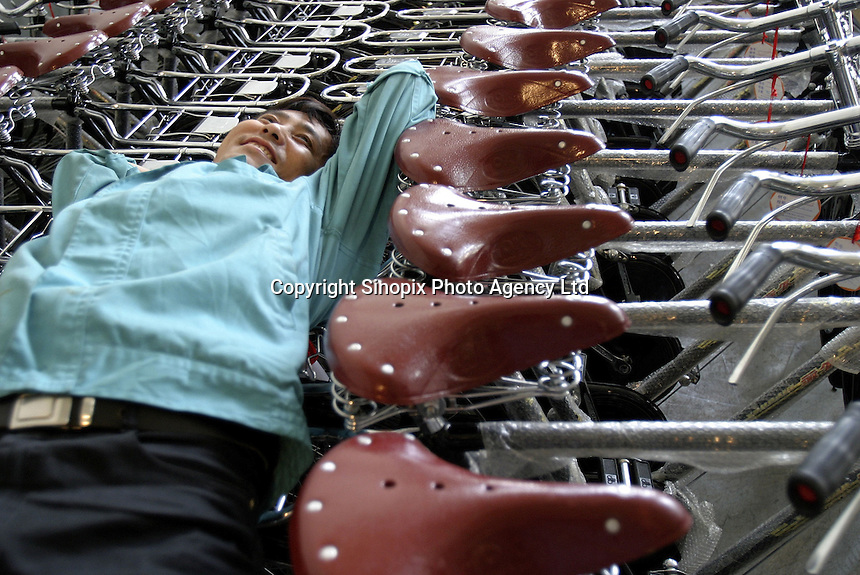 A worker takes an after-lunch siesta laying on top of tightly packed bicycles at the Shanghai Forever Bicycle Factory (SFBF) in Shanghai, China. Despite the government's efforts to encourage automobile ownership in recent years, the bicycle remains the most popular mode of transportation for China's masses. The SFBF, it's products once a must have and a symbol of status for every Chinese family, are now supplying bicycles to countries around the world. It has seen it's sales increase 59% percent in the past year to 876 million yuan (euro 89.36 million)..21-APR-04