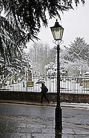 Woman with umbrella walks past snow covered graveyard, Hampstead, North London, United Kingdom