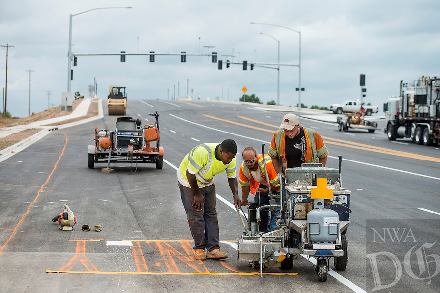 STAFF PHOTO ANTHONY REYES<br />Alvin Benson, from left, Michael Wheeler and Josh Kelly stripe letters for a turn lane Friday, June 27, 2014 on Don Tyson Parkway near the nearly completed Don Tyson Parkway interchange in Springdale. The road will provide a new access to Interstate 49 on a major road through Springdale and will provide easy access to Arvest Ballpark and any new construction in the immediate area. Walmart just announced they will build a new Neighborhood Market in the area.