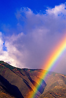 A rainbow over the West Maui Mountains south of Lahaina town; The highest point of the West Mauis is an extinct volcano with a 5,788-ft. elevation. It is considered one of the wettest spots on planet Earth with over 400 inches of annual rainfall.
