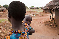 A young girl  carryinga  baby in Madi Opei, Uganda.