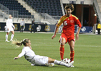 Heather Mitts #2 of the USA WNT slides into Ling Sun #15 of the PRC WNT during an international friendly match at PPL Park, on October 6 2010 in Chester, PA. The game ended in a 1-1 tie.