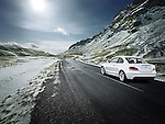 One white 2012 BMW 1series 135 Coupe driving on a high mountain winter road.