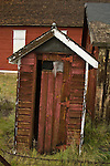 Weathered red wooden outhouse with painted crescent moon behind the Dist. 11 Schoolhouse, Leadville, Colorado.
