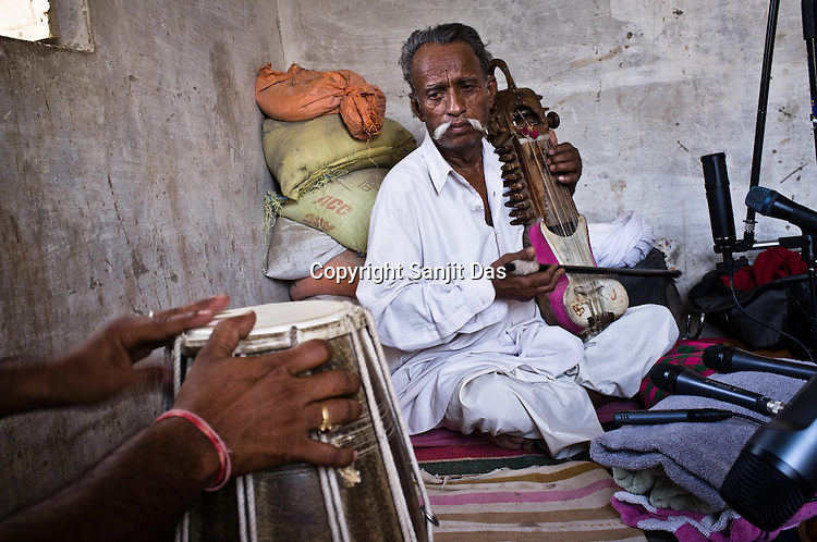 66-year-old Manganiyar artist, Lakha Khan plays the Sarangi (musical instrument) while his eldest son, Dane Khan (left) accompanies him with Dholak in their house in Raneri village of Jodhpur district in Rajasthan, India. Photo: Sanjit Das/Panos .