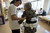"""Robot HAL at Akanekai Showa HOSPITAL.http://www.akanekai-showa.com.Rehabilitation Section at the Showa hospital uses these HAL legs to help elderly that have a hard time walking.  These are ACTUALLY in use on a daily basis... outpatients (usually) come in twice a week and have a number of electrodes placed in key areas on their legs and lower torso.  These electrodes monitor minor changes in muscle activity and transfer that information to the robotic joints.  Woman being put into the legs is:.EMOTO (Last Name), Chiyoko (89) : She had a fracture of right and left thighbone.The main woman therapist working with her is TSURUGA (Last Name), Mai (P.T.).All of these robotics folks developing robots for elderly talk about studies showing that more and more elderly are isolated and have no one to relate to... In 2009 it was 19 percent of the elderly population of Japan.  They have a word for it:  """"Kodokushi"""" or """"lonely death.""""."""