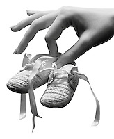 Female hand holding a pair of baby shoes.