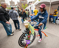 "A volunteer from Sustainable America uses a bicycle powered blender Union Square Park in New York on Tuesday, May 10, 2015 to make vegetable based smoothies as part of the ""Feeding the 5000"". The public was treated to a free lunch made of high quality produce that normally would have been thrown out from the restaurants and stores that supplied them. ""Feeding the 5000"" was meant to educate the public to help eliminate food waste. (© Richard B. Levine)"
