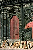Firewood drying near ornate carved wooden doorway, Bhaktapur, Nepal