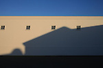 A shadow from a nearby winery is cast upon a warehouse in Napa Valley, California.