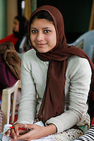 Dehradun, India.  Young Muslim Woman with nose ring holding embroidered pillow case on her lap.