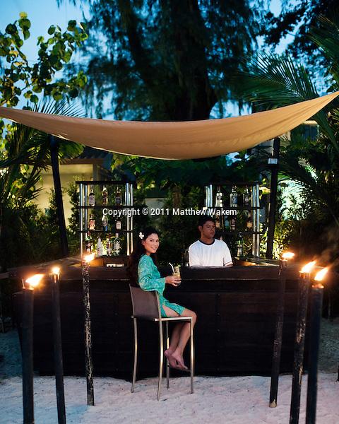 Woman at Beach Bar at Indigo Pearl, Phuket, Thailand. A woman sits at Indigo Pearl's Beach Club Bar on Nai Yang Beach at dusk. Phuket, Thailand.