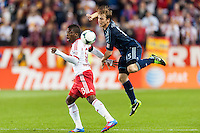 Marius Obekop (13) of the New York Red Bulls and Seth Sinovic (15) of Sporting Kansas City go for the ball. Sporting Kansas City defeated the New York Red Bulls 1-0 during a Major League Soccer (MLS) match at Red Bull Arena in Harrison, NJ, on April 17, 2013.