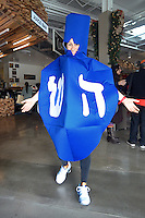 Julia Moss dressed in a Dreidel costume spins during  the Chanukah Celebration at Santa Monica Place on Sunday, December 9, 2012.