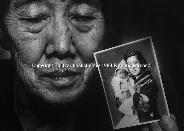 "Shizuki Itoh, 79, holds up a photograph of her and her infant daughter, taken 45 years ago. Two years after the bombing, and one year after Itoh's husband died of kidney failure, her daughter died of radiation sickness. One woman, Shizuka Itoh, had a little daughter only 17 months old.  In the nine months that followed the devastation of the bomb, the daughter seemed tortured with pain. There was nothing the doctors could do. The daughters kept losing hair, vomiting, crying constantly.  Other children were dying all around.  ""As Itoh held her daughter in her arms one day in May, she cried out to her, ""Go to the gods.""  ""The 2-year-old grabbed at Itoh's neck and died.  Itoh tried to commit suicide the next year.  ""I have never told this story to anyone, she told me in a quiet voice."" Pulitzer finalist entry 1989 Frederic Larson©"
