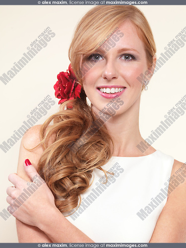 Portrait of a smiling attractive young woman with long blond hair isolated on beige background