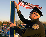 Seattle Police officer Jeff Mitchell pins a department patch to a memorial board near flowers, balloons and wreaths at a makeshift memorial to four slain police officers at the Forza Coffee Shop  in Lakewood, Washington, USA, on 2 December  2009. Four Lakewood officers were gunned down during a morning meeting at a local coffee shop on 29 November 2009.  Jim Bryant Photo. ©2010. ALL RIGHTS RESERVED.