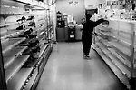An elderly woman searches for food to buy among empty shelves in a convenience store after the earthquake, tsunami and nuclear power plant crisis meant that the most important supply routes north were closed and impassable to trucks carrying cargo.  Bottled water, gasoline, kerosene and food became scarce closer to the tsunami zone.  Kitakami, Iwate Prefecture, Japan.