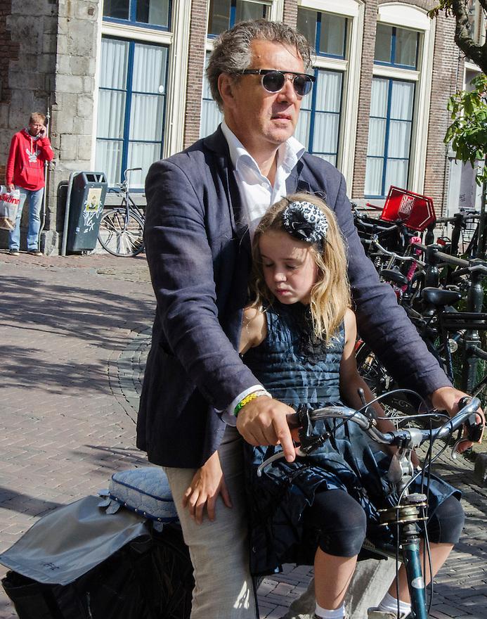Netherlands, Utrecht, 12 sept 2014<br /> Vader met dochter voor op de fiets. Op de stang van de fiets is een zitje gemonteerd waar het meisje op zit. Een hand ligt aandoenlijk lief op het been van haar vader.<br /> Foto: (c) Michiel Wijnbergh