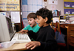 Oakland CA Boys, eight-years-old excited over results on computer they're using in class