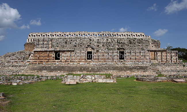 """Western façade of the Codz Poop (""""Rolled-up matting"""" in Maya), Altar of the Glyphs and Chultun of the God Chaac in the foreground, originally covered with 250 stone masks of Chaac, the big-nosed god of rain, Puuc Architecture, 700-900 AD, Kabah, Yucatan, Mexico. Picture by Manuel Cohen"""