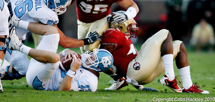 TALLAHASSEE, FL 11/6/10-FSU-NC FB10 CH-Florida State's Brandon Jenkins, right, sacks North Carolina's T.J. Yates for  a 10-yard loss at the close of first half action Saturday at Doak Campbell Stadium in Tallahassee. The Tar Heels beat the Seminoles 37-35. .COLIN HACKLEY PHOTO