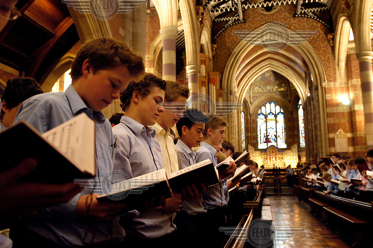 Pupils singing during the morning service in the chapel at Rugby School, one of the oldest public (private) schools in England.