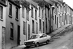 Derry Northern Ireland Londonderry. 1979. In the Waterside area, houses boarded up families moved out of town due to sectarian violence, all apart from one home. A child leaves the front door.