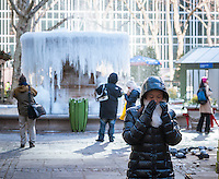 Visitors to Bryant Park in New York stop at the Josephine Shaw Lowell Memorial Fountain which has become a cold weather ice sculpture on Thursday, January 8, 2015. Temperatures in the city are in the single digits and low teens with the wind making it seem like 15 degrees below zero. (© Richard B. Levine)
