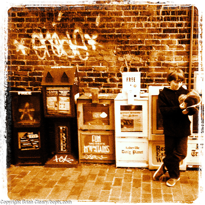 A boy leans against a line of newspaper machines in Asheville, NC, iPhone photo from the instagram photostream of bcpix. (Photo by Brian Cleary/www.bcpix.com)