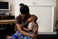 """Thania, from DR Congo, with one of her two children born after she was forced into prostitution, in the bedsit where she now stays. She arrived in the UK in September 2004 claiming asylum after her family were murdered by Congolese soldiers. She was forced to watch her brother burned to death after a tyre was set alight around his neck. She was raped but managed to escape. After her claim was refused she walked the streets begging people for food and money, """"I couldn't think properly because I was so hungry."""" Thania is one of an estimated 300,000 rejected asylum seekers living in the UK. ."""