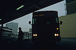 Silhouetted older woman getting ready to board a bus going to the race track downtown bus terminal Seattle Washington State USA