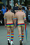 a gay male couple, from behind, walk hand in hand wearing rainbow swim suits and knee socks, after the Seattle Gay Pride rally