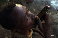 Yaeda Valley, Tanzania: Gonga Gonga, a Hadzabe man, smokes ganga, or marijuana, at his settlement in the hills surrounding this Northern Tanzania valley. The Hadzabe are one of the last tribes of hunter gatherers on Earth, but their way of life is under enormous pressure from encroaching pastoral tribes, and a safari company that wants to use their tribal land for hunting. The valley once teemed with wild animals but in recent decades, populations have declined sharply due to poaching and competition for grazing land and water. Gonga Gonga, who once killed two zebra, an antelope and a buffalo in one day, can now go a week without killing a single animal. (PHOTO: MIGUEL JUAREZ LUGO)