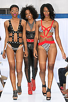 Fashion designer Adisa Imani Christopher walks runway with models at the close of her AdianiC Spring 2013 fashion show, during the JRG Bikini Under The Bridge 2012 fashion show on July 9, 2012.
