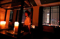 A young woman walks by as the Oriental Pearl TV Tower is seen in a window in Lounge 18 bar in Shanghai, China, on May 9, 2008. Lounge 18 bar is part of the Bund 18 building. Photo by Lucas Schifres/Pictobank
