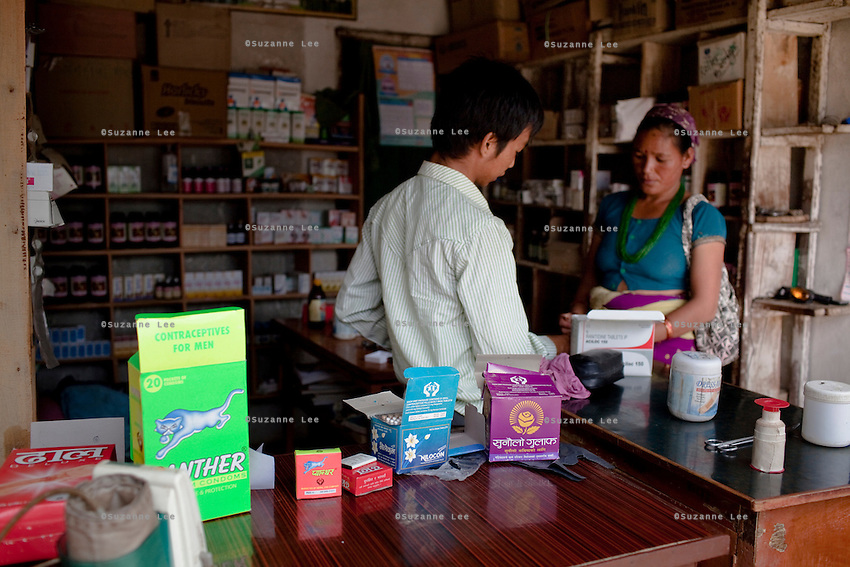 Boxes of a variety of contraceptives lie on the countertop as Rana Bahadur Magar (left), 24, attends to a customer in his pharmacy which he bought over 2 years ago in Gangate Village, Sathakhani Bidishi, Surkhet district, Western Nepal, on 30th June 2012. Monthly, Rana Bahadur Magar sells over 300 condoms and 1700 birth control pills and does about 10 injections of 3-month-long contraceptives which he is trained to do. The nearest district hospital is an hour's drive away. In Surkhet, StC partners with Safer Society, a local NGO which advocates for child rights and against child marriage.  Photo by Suzanne Lee for Save The Children UK