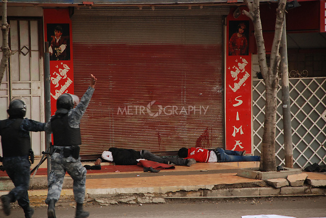 SULAIMANIYAH, IRAQ: Kurdish Iraqi police run towards two bodies lying in front a shuttered storefront...Kurdish security forces shot and killed protesters in the northern Iraqi city of Sulaimaniyah...Photo by Sartep Osman
